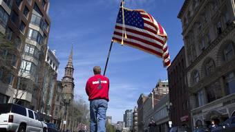 Feuerwehr-Leutnatn Mike Murphy trägt eine Woche nach dem Attentat eine amerikanische Flagge durch jene Strassen, in denen während des Marathons ein Bombenattentat erfolgte.