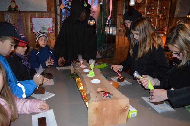 Die Kinder besuchen den Samichlaus in seinem feierlich geschmückten «Hüsli» an der Holzgasse in Hausen; die Kinder verzieren ihre Lebkuchen.