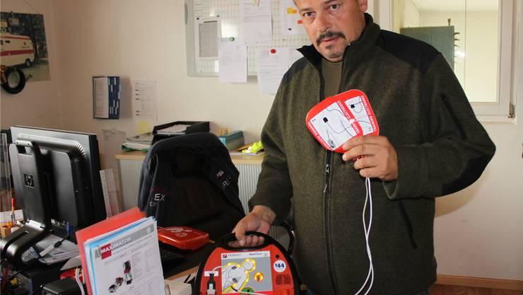 Reinhard Grichting, Leiter Rettungsdienst, zeigt ein Defibrillator-Demogerät für Herznotfälle.