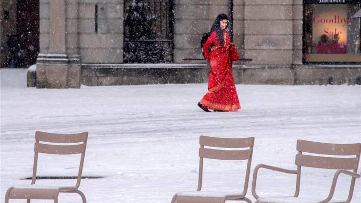 Überrascht vom Schnee: Die Frau im roten Kleid huscht davon.Frank Studer