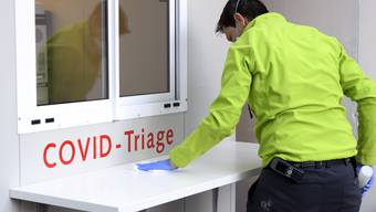Ein Spital-Mitarbeiter reinigt eine COVID-Triage im Berner Inselspital.