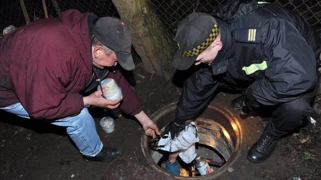 Polizist in Polen reicht einem Obdachlosen Essen (Symbolbild)