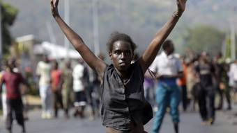 Demonstrantin mit erhobenen Armen in Bujumbura
