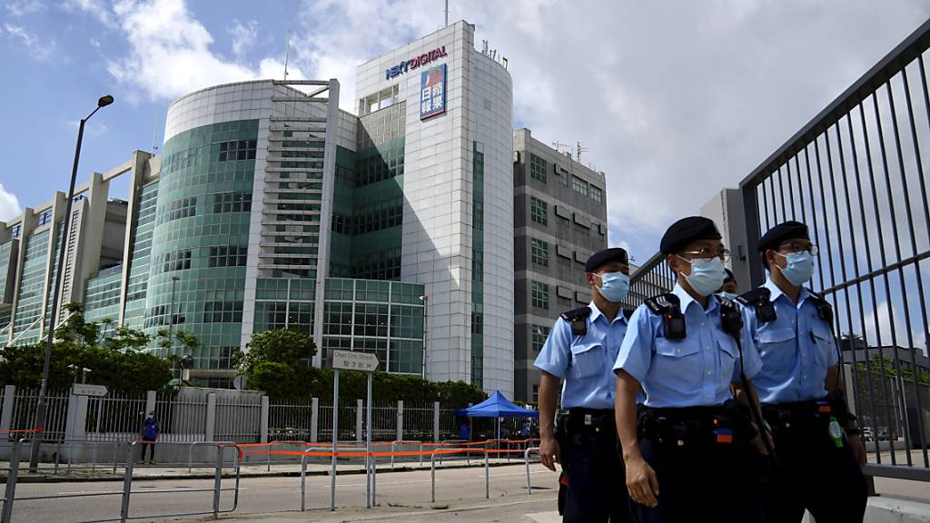 Polizisten gehen vor dem Hauptquartier der pro-demokratischen Zeitung Apple Daily. Fünf Führungskräfte der pro-demokratischen Hongkonger Zeitung «Apple Daily» sind am Donnerstag wegen angeblicher Verstöße gegen das umstrittene Sicherheitsgesetz festgenommen worden. Foto: Kin Cheung/AP/dpa