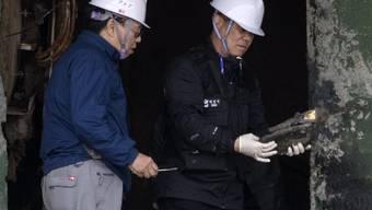 Experten betrachten ein Fundstück aus der gesunkenen Fähre Sewol. Arbeiter wollen darin nun erstmals menschliche Knochenfragmente entdeckt haben. (Archiv)