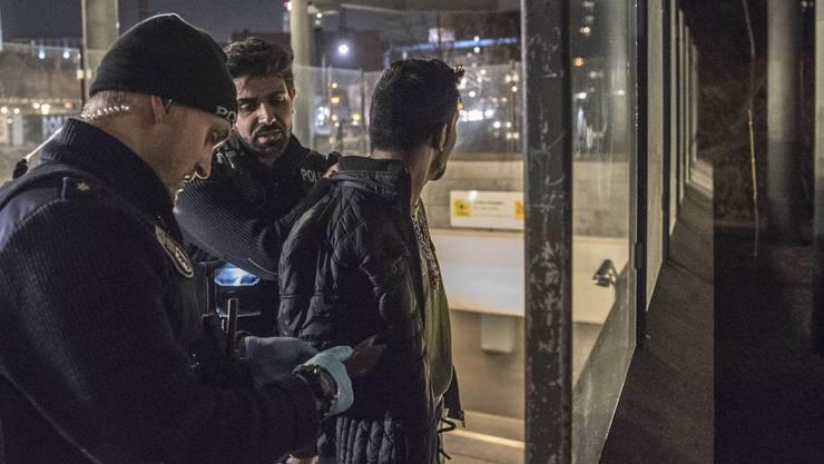 Zwei Polizisten durchsuchen einen ihnen bekannten Mann an der Jannowitzbrücke.