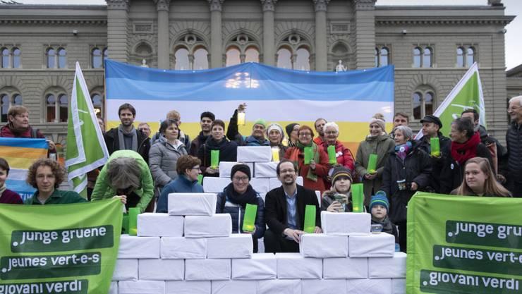 Balthasar Glättli (GPS/ZH) und Aline Trede (GPS/BE) posieren mit Mitgliedern der Grünen und jungen Grünen bei der Einreichung der Gletscherinitiative am Mittwoch auf dem Bundesplatz in Bern.