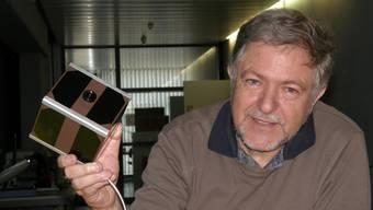 Professor Jörg Sekler zeigt stolz das Modell von Swiss Cube: Der  würfelförmige Minisatellit hat eine Kantenlänge von 10 Zentimetern.