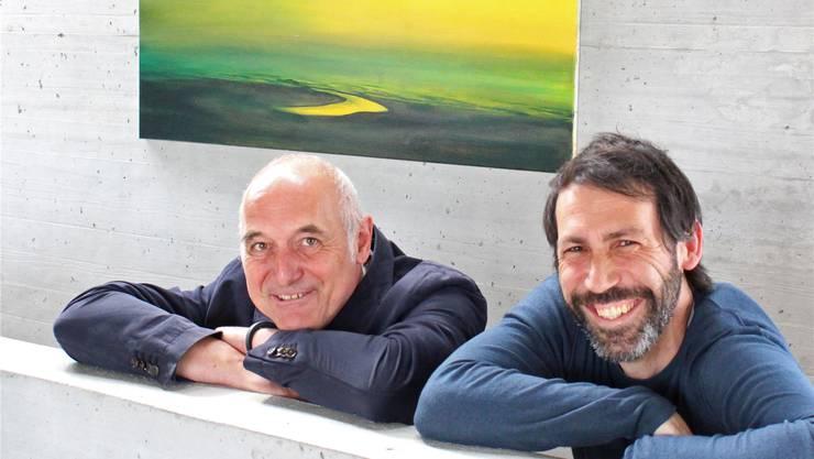 Künstler Andreas Camenisch (rechts) und Hausherr Fugo Diethelm vor einem Landschaftsbild in Grün- und Gelbtönen.Cornelia Bisch