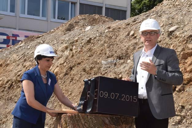 Zafiro Hausheer, Leitende Ärztin Stationärer Bereich, und Gesamtprojektleiter Thomas Zweifel mit der Kiste, die in der Bodenplatte einbetoniert wird