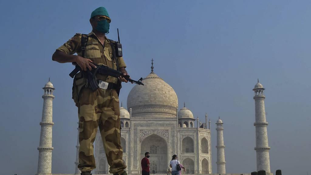 ARCHIV - Ein paramilitärischer Soldat trägt eine Stoff-Maske und patrouilliert vor dem Taj Mahal. Foto: Pawan Sharma/AP/dpa