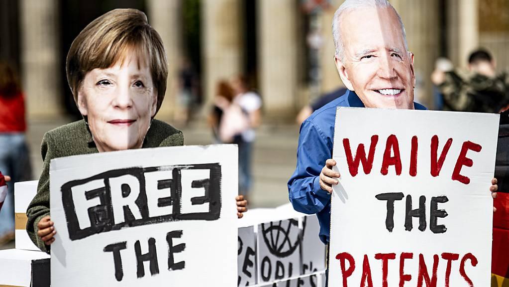 Aktivisten mit Masken, die Bundeskanzlerin Merkel und den US-Präsidenten Biden darstellen, stehen vor dem Brandenburger Tor in Berlin. Die Aktivisten fordern die vorübergehende Aussetzung des Patentschutzes für die Covid-Impfstoffe. Foto: Fabian Sommer/dpa