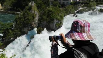 Eine Touristin geniesst die Aussicht auf den Rheinfall (Archiv)