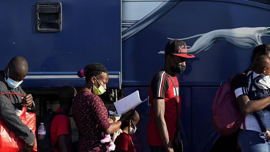 Migranten bereiten sich darauf vor, einen Bus zu besteigen, nachdem sie in einem behelfsmäßigen Lager nahe der Internationalen Brücke in Del Rio abgefertigt und entlassen wurden. Die USA wollen angesichts Tausender Migranten in der US-Grenzstadt Del Rio die Menschen schnell außer Landes bringen. Foto: Eric Gay/AP/dpa