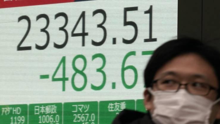 An den Börsen geht es wegen dem Coronavirus abwärts: ein Mann mit einer Maske in Tokio vor einer Börsenanzeigetafel.