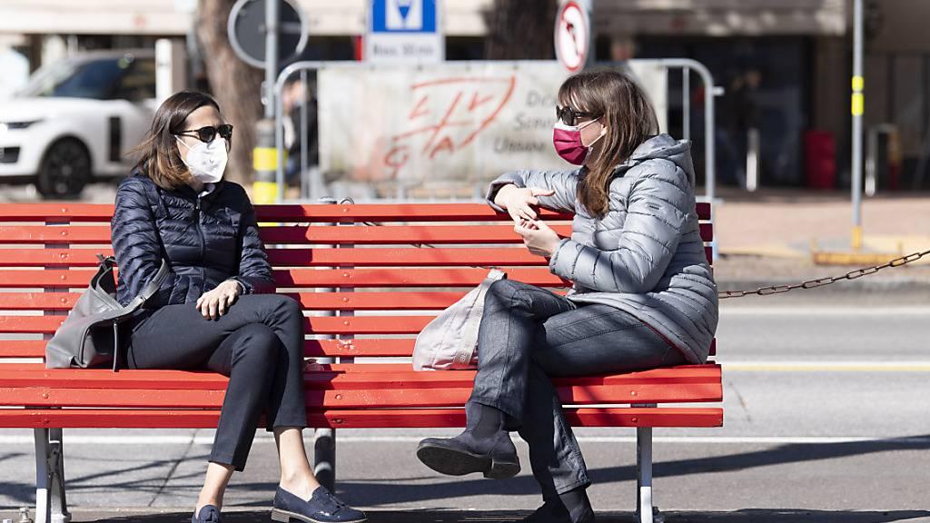 Schutzmasken gehören mittlerweile zum Alltag, so wie hier in Lugano, wo zwei Frauen auf einer Sitzbank verweilen. (Themenbild)