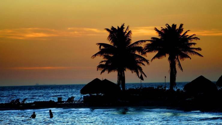 Touristen geniessen den Sonnenuntergang an einem Strand in Curaçao in den Niederländischen Antillen.
