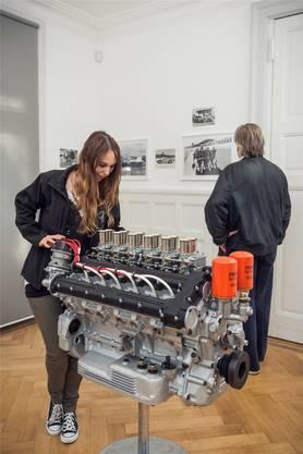 Neue Rollen: Die junge Frau beugt sich übers Herzstück der Ausstellung, einen Ferrari-Motor. Der alte Automuffel widmet sich zeitlos menschlichen Geschichten.