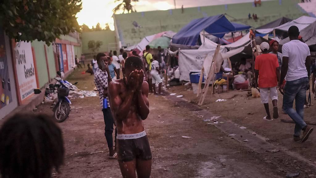 Menschen, die bei dem Erdbeben ihre Häuser und Wohnungen verloren haben, drängen sich in notdürftigen Unterkünften, während sich sich über ihnen der Himmel verdüstert. Der tropische Sturm Grace soll in der Nacht über das Erdbebengebiet ziehen.