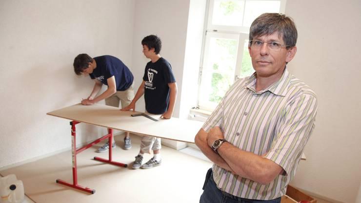 Christof Koch, Leiter Schulen im Bachtelen, darf zufrieden sein. Im Hintergrund zwei Lehrlinge, die Innenausbau-Schreinerarbeiten erledigen.
