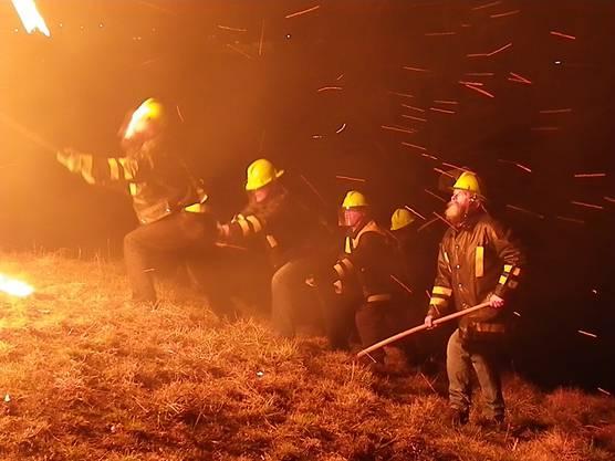 """In der Gluthitze und im Funkenregen stehend treiben die """"Schiibespränger"""" das Feuer-rad an, kritisch beobachtet von Sepp Hauswirt."""