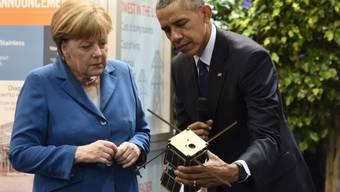 Merkel und Obama betrachten an der Messe einen kleinen Satelliten.