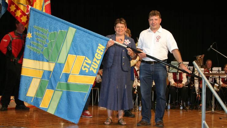 Neuer Begleiter: Fahnengotte Pia Hürbin und Fahnengötti Daniel Hollinger zeigen die neue Fahne der Zuzger Turnerschar. (Hans Zemp)