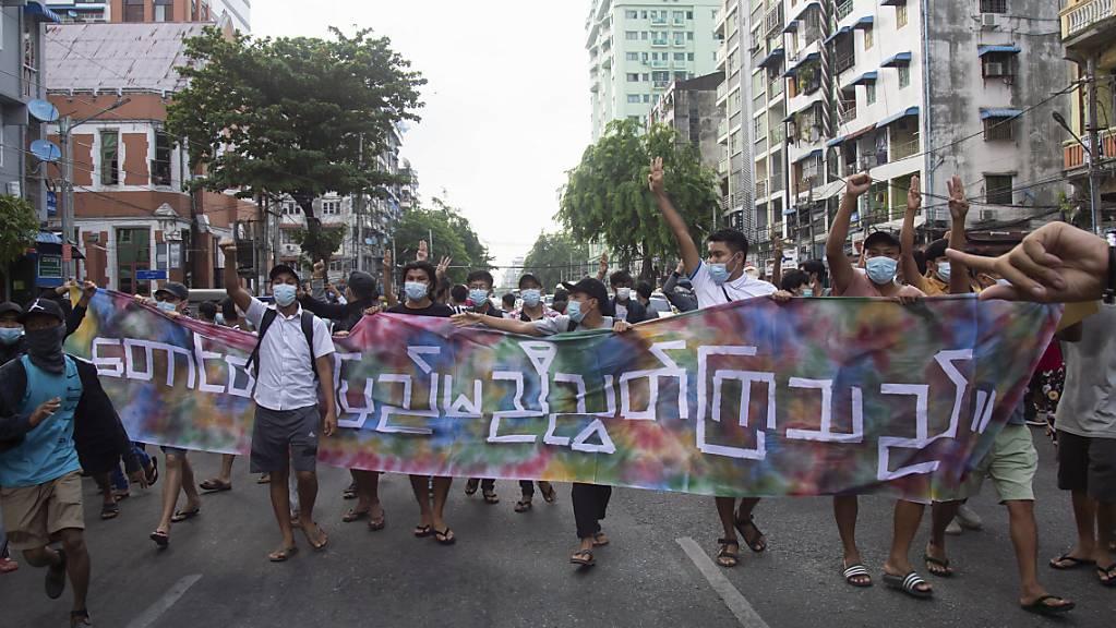 Anti-Putsch-Demonstranten mit der Aufschrift «Berge und Festland sind vereint» in Yangon. Foto: AP/dpa