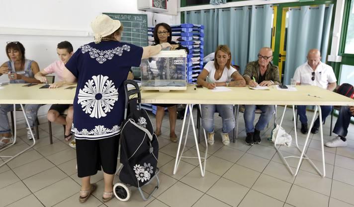 Eine Frau gibt ihren Wahlzettel in Marseille ab.