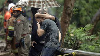 A relative of missing persons is comforted by a friend at a site where rescue workers search for victims after heavy rains in Rio de Janeiro, Brazil, Tuesday, April 9, 2019. Heavy rains blamed for the deaths of at least six people continued to fall on Rio on Tuesday as officials closed schools and urged people to avoid non-essential traffic. (AP Photo/Silvia Izquierdo)