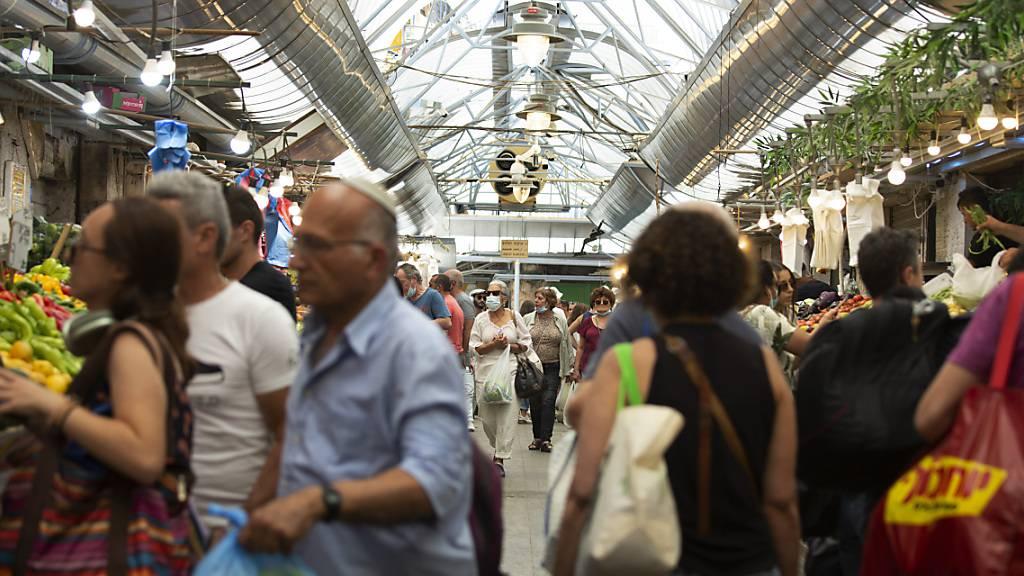Menschen tragen Schutzmasken, während sie auf dem Mahane Yehuda Markt in Jerusalem einkaufen. Foto: Maya Alleruzzo/AP/dpa