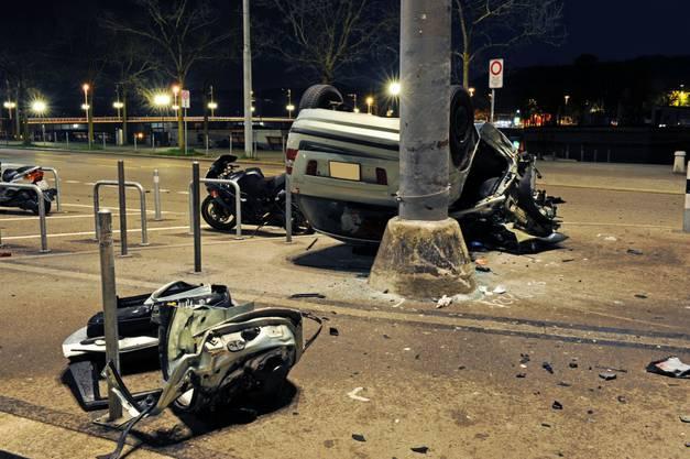 DAs Auto des vor der Polizei fliehenden kollidierte mit dem Masten, der Wagen wird dabei zertrümmert und aufs Dach gedreht.