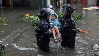 Zwei Polizisten retten ein kleines Mädchen aus seinem Zuhause in Hongkong. Der Taifun soll der schlimmste seit Aufzeichnung der Wetterdaten sein.
