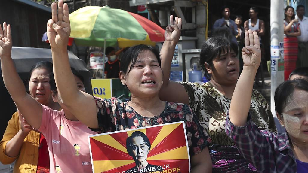 Frauen mit einem Portrait der abgesetzten myanmarischen Regierungschefin Aung San Suu Kyi während eines Protests gegen den Militärputsch. Foto: Str/AP/dpa