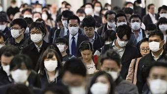 Die grosse Frage lautet: Wer hat das Virus, und wer ist schon immun? Pendler in einem Bahnhof in Tokio.