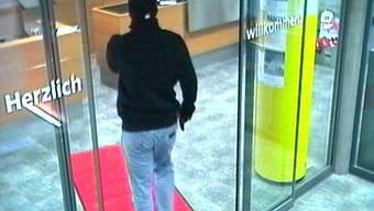Der unbekannte Täter betritt die Raiffeisenbank in Muhen beim Überfall.