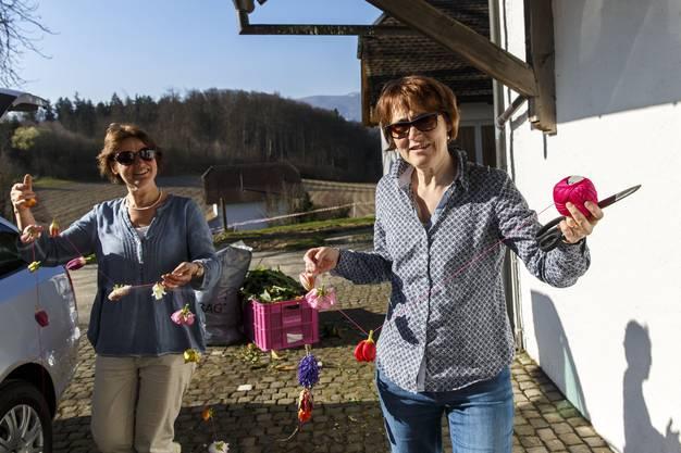 Maria Zimmerli und Heidi Bisang tragen Blumengirlanden ins Schlösschen