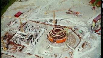 Die Nordostschweizerischen Kraftwerke (NOK) entschieden sich 1964 für die Kernenergie. Auf einer künstlichen Insel in der Aare auf Gemeindegebiet von Döttingen wird danach das Atomkraftwerk Beznau gebaut. Das Bild oben ist eine Luftaufnahme von Süden aus dem Jahr 1966, es zeigt das erste Reaktorgebäude (orange) im Bau. Bild: Comet Photo, ETH Bildarchiv