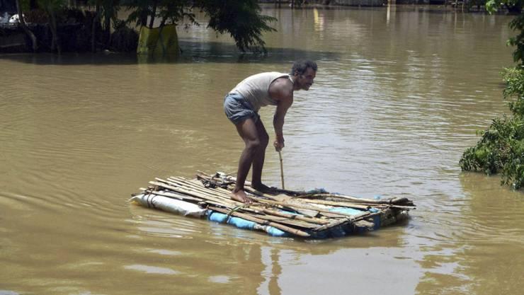 Dieser Mann weiss sich selbst zu helfen; ein ranghoher Politiker liess sich bei einem Besuch in den indischen Überschwemmungsgebieten dagegen von Polizisten tragen.