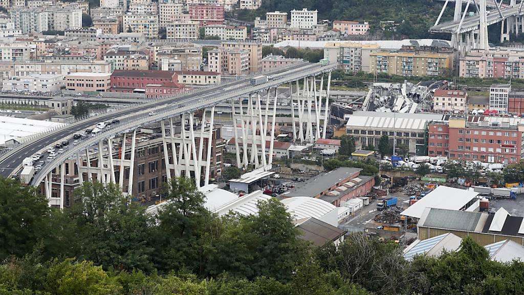 ARCHIV - Autos stehen auf der teilweise eingestürzten Autobahnbrücke Ponte Morandi. Autos und Lastwagen stürzten in die Tiefe. 43 Menschen starben. Mehr als zwei Jahre nach dem tödlichen Brückeneinsturz ist die Polizei gegen sechs ehemalige und aktuelle Manager des Autobahnbetreibers vorgegangen. Foto: Antonio Calanni/AP/dpa
