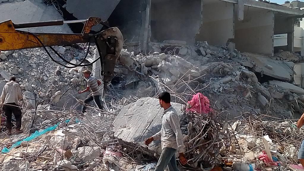 Palästinensische Männer arbeiten auf einem Grundstück in Gaza-Stadt, um Folgen der Zerstörungen durch Luftangriffe während des Konflikts im Mai zu beseitigen. 100 Tage nach der Waffenruhe zwischen Israel und der in Gaza herrschenden Hamas steht der Wiederaufbau noch am Anfang. Foto: Eva-Maria Krafczyk/dpa