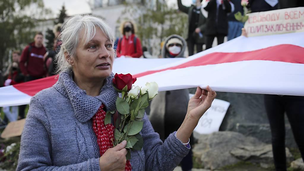 Eine Frau hält bei einer Demonstration Rosen und die historische weiss-rot-weisse Fahne in der Hand. Tausende Menschen, darunter vor allem Senioren und Studenten, marschierten am Montag durch die Hauptstadt.
