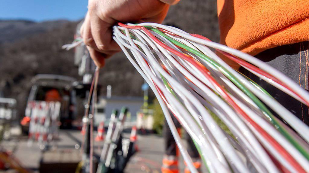 Ein Arbeiter montiert Glasfaserkabel der Swisscom. Die Comcom stützt sich bei der Preisberechnung für die Mitbenützung des Swisscom-Netzes neu auf die Kosten für Glasfaserleitungen. (Archiv)