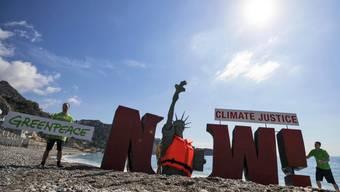 Greenpeace warnt mit einer am Strand auf Sizilien versinkenden Freiheitsstatue vor dem Zuwarten im Kampf gegen den Klimawandel