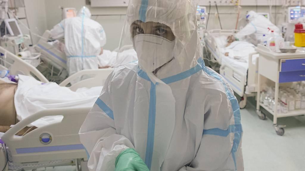 Eine medizinische Mitarbeiterin richtet ihre Handschuhe auf der Corona-Intensivstation. Foto: Vadim Ghirda/AP/dpa