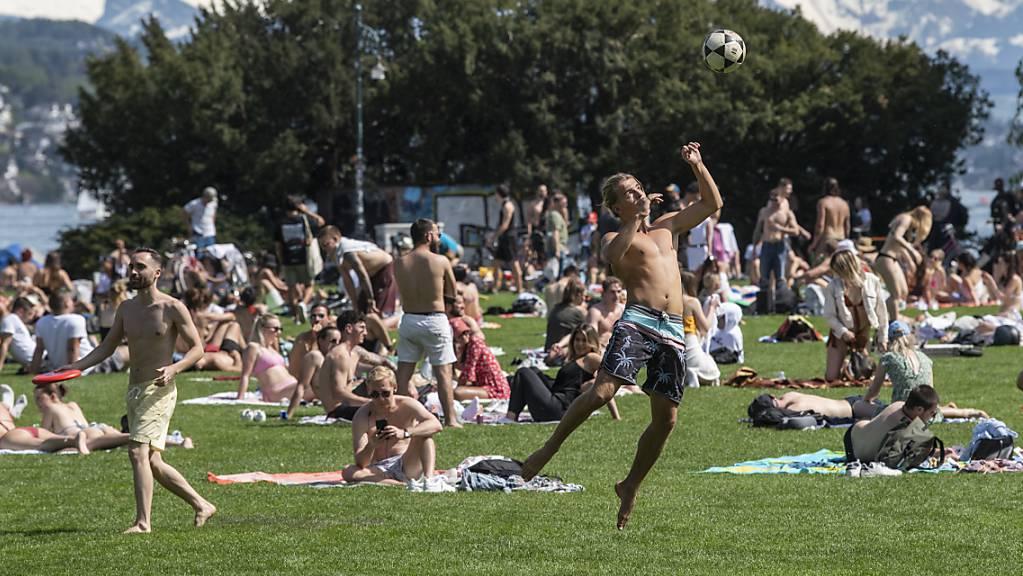 Die Bevölkerung geniesst das sommerliche Wetter am Sonntag, wie hier am See in Zürich.