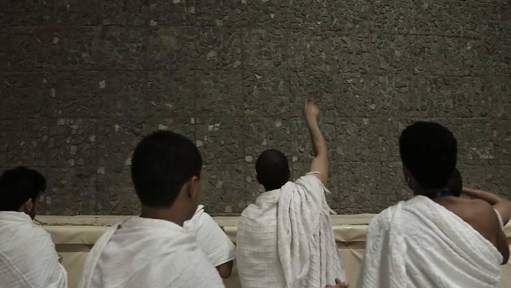 Saudiarabische Pilger werfen in Mina Steine gegen eine Säule und steinigen so symbolisch den Teufel.
