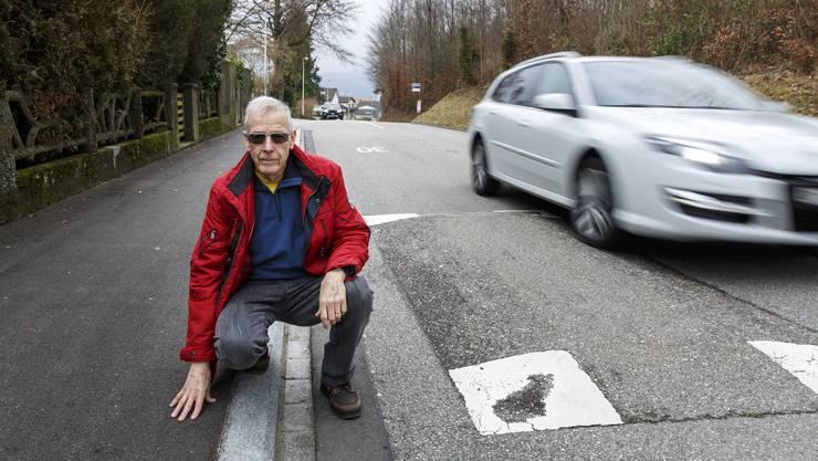 Robert Bennett neben der Bodenschwelle, bei der das Trottoir erhöht wurde. So können die Fahrzeuge nicht mehr aufs Trottoir ausweichen.