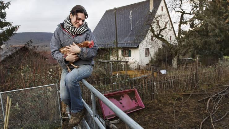 Martina Blattner mit dem Huhn «Sherpa» – im Hintergrund der Hof in dem sie seit 10 Jahren lebt und arbeitet.