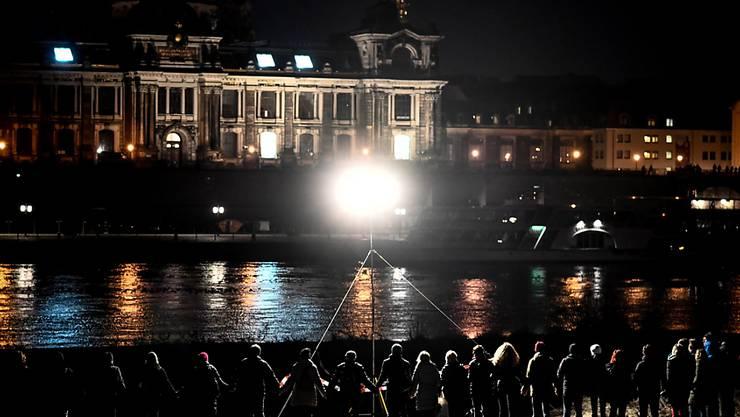 Im Gedenken an die Zerstörung ihrer Stadt: Dresdnerinnen und Dresdner in einer Menschenkette an der Elbe.